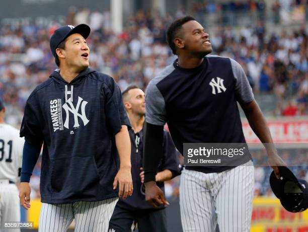 Pitchers Masahiro Tanaka and Luis Severino of the New York Yankees walk in from the bullpen enjoying a laugh before the start of an MLB baseball game...