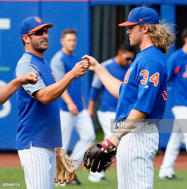 Pitchers Matt Harvey and Noah Syndergaard of the New York Mets punch fists after the two injured starters threw baseballs to each other for the first...