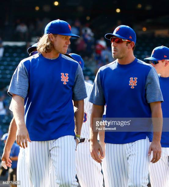 Pitchers Noah Syndergaard and Matt Harvey of the New York Mets talk as they leave the field after celebrating the Mets win in an MLB baseball game...