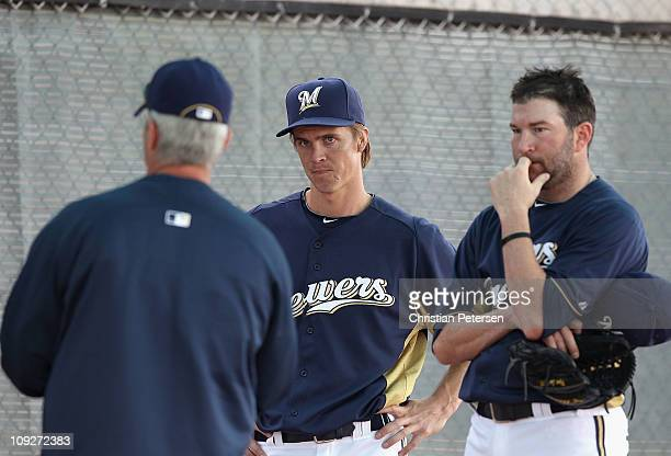 Pitchers Zack Greinke and Shaun Marcum of the Milwaukee Brewers listen to pitching coach Rick Kranitz during a MLB spring training practice at...