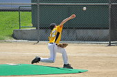 A young boy pitching a strike in a baseball game.