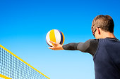 Beach volleyball player concentrates to pitch the ball over the net
