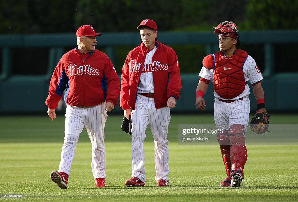 Pitching coach Bob McClure starting pitcher Jeremy Hellickson and catcher Carlos Ruiz of the Philadelphia Phillies walk in from warming up in the...