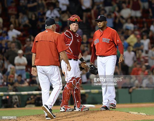Pitching coach Carl Willis of the Boston Red Sox visits the mound to speak with Fernando Abad and Bryan Holiday in the ninth inning against the...