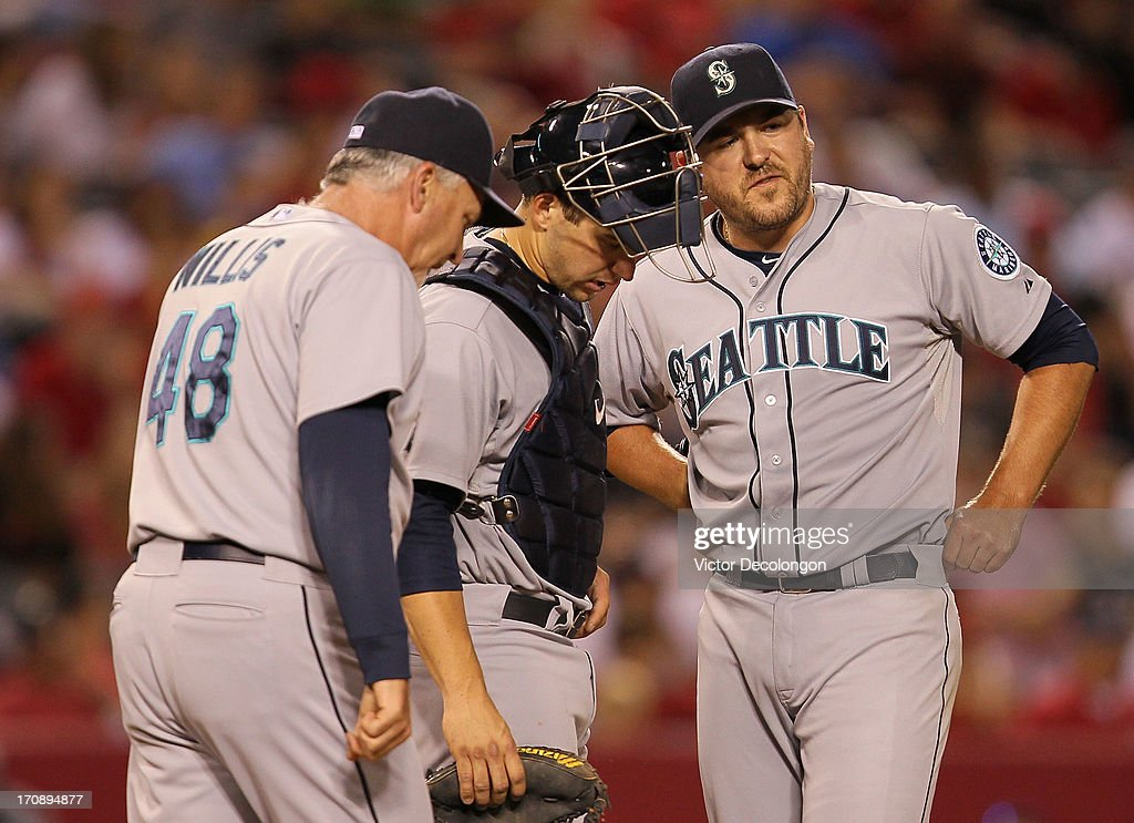 Pitching coach Carl Willis #48 of the Seattle Mariners walks to the mound to have a word with catcher <a gi-track='captionPersonalityLinkClicked' href=/galleries/search?phrase=Mike+Zunino&family=editorial&specificpeople=6803368 ng-click='$event.stopPropagation()'>Mike Zunino</a> #3 and pitcher <a gi-track='captionPersonalityLinkClicked' href=/galleries/search?phrase=Joe+Saunders&family=editorial&specificpeople=835979 ng-click='$event.stopPropagation()'>Joe Saunders</a> #23 in the eighth inning during the MLB game against the Los Angeles Angels of Anaheim at Angel Stadium of Anaheim on June 19, 2013 in Anaheim, California. The Angels defeated the Mariners 1-0.