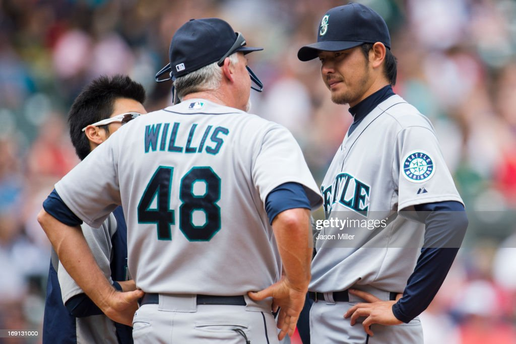 Pitching coach Carl Willis #48 talks with starting pitcher Hisashi Iwakuma #18 of the Seattle Mariners after Iwakuma gave up two homers for four runs during the second inning against the Cleveland Indians at Progressive Field on May 20, 2013 in Cleveland, Ohio.