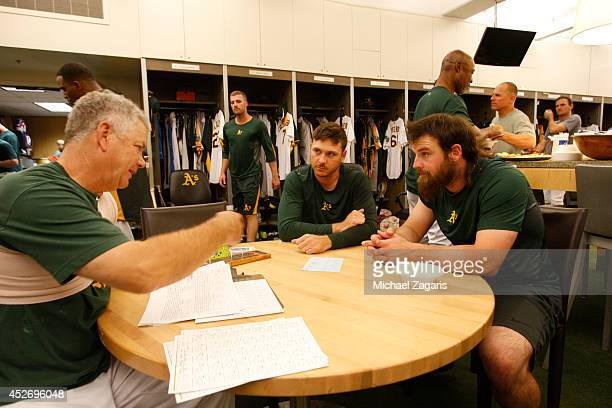 Pitching Coach Curt Young of the Oakland Athletics goes over hitters with Scott Kazmir and Derek Norris in the clubhouse prior to the game against...