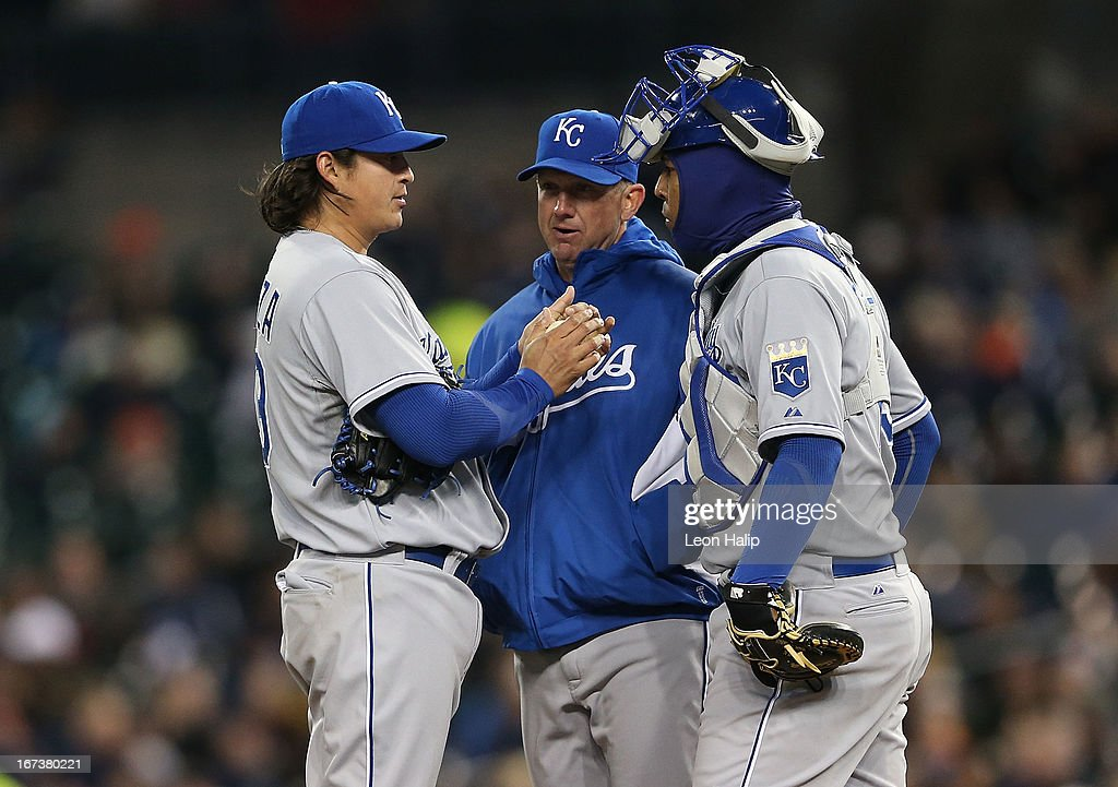 Pitching coach Dave Elland of the Kansas City Royals talks with pitcher Luis Mendoza and catcher Salvador Perez during the fourth inning of the game...