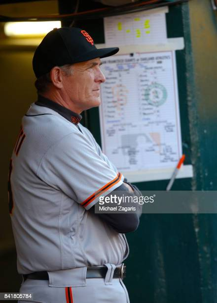 Pitching Coach Dave Righetti of the San Francisco Giants stands in the dugout during the game against the Oakland Athletics at the Oakland Alameda...