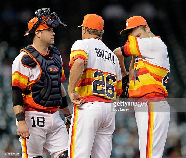 Pitching coach Doug Brocail of the Houston Astros talks with Jordan Lyles of the Houston Astros and Chris Snyder of the Houston Astros during a...