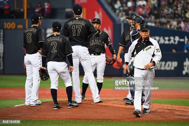 Pitching Coach Hiroshi Gondoh of Japan walks down the mound after talking to pitcher Shintaro Fujinami in the bottom of the first inning during the...