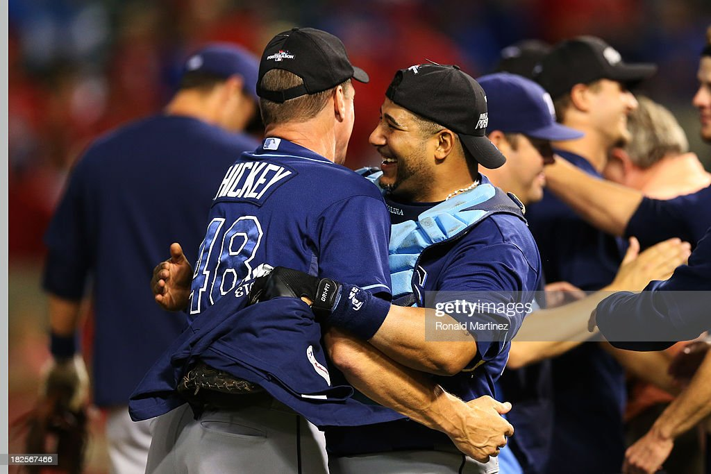 Pitching coach Jim Hickey #48 and Jose Molina #28 of the Tampa Bay Rays celebrate their 5 to 2 win over the Texas Rangers in the American League Wild Card tiebreaker game at Rangers Ballpark in Arlington on September 30, 2013 in Arlington, Texas.