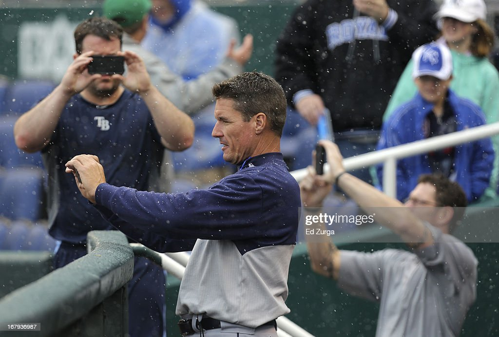 Pitching coach Jim Hickey (in front) of the Tampa Bay Rays and other members of the team take photos of snow falling during a game delay against the Kansas City Royals at Kauffman Stadium on May 2, 2013 in Kansas City, Missouri. The game was postponed due to weather.