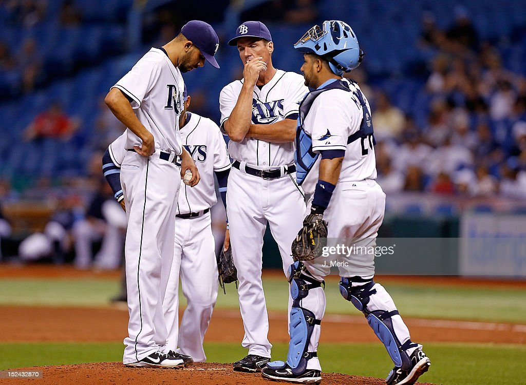 Pitching coach <a gi-track='captionPersonalityLinkClicked' href=/galleries/search?phrase=Jim+Hickey&family=editorial&specificpeople=643232 ng-click='$event.stopPropagation()'>Jim Hickey</a> #48 of the Tampa Bay Rays talks with pitcher <a gi-track='captionPersonalityLinkClicked' href=/galleries/search?phrase=David+Price+-+Baseball+Player&family=editorial&specificpeople=4961936 ng-click='$event.stopPropagation()'>David Price</a> #14 as catcher <a gi-track='captionPersonalityLinkClicked' href=/galleries/search?phrase=Jose+Molina&family=editorial&specificpeople=206365 ng-click='$event.stopPropagation()'>Jose Molina</a> #28 look on against the Boston Red Sox during the game at Tropicana Field on September 20, 2012 in St. Petersburg, Florida.