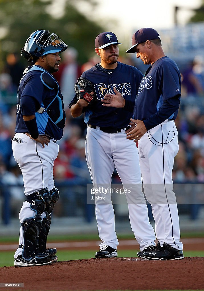 Pitching coach Jim Hickey #48 (right) of the Tampa Bay Rays talks with pitcher Matt Moore #55 and catcher Jose Molina #28 during a Grapefruit League Spring Training Game against the Pittsburgh Pirates at the Charlotte Sports Complex on March 25, 2013 in Port Charlotte, Florida.