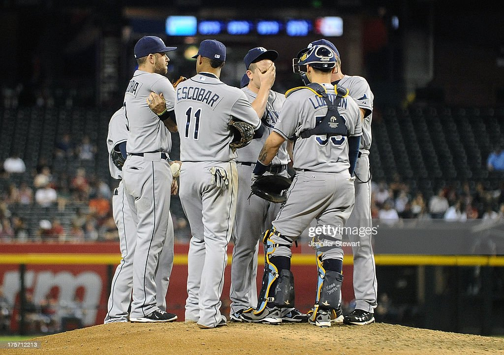 Pitching coach <a gi-track='captionPersonalityLinkClicked' href=/galleries/search?phrase=Jim+Hickey&family=editorial&specificpeople=643232 ng-click='$event.stopPropagation()'>Jim Hickey</a> #48 of the Tampa Bay Rays talks with pitcher <a gi-track='captionPersonalityLinkClicked' href=/galleries/search?phrase=Jeremy+Hellickson&family=editorial&specificpeople=2364859 ng-click='$event.stopPropagation()'>Jeremy Hellickson</a> #58 and infielders on the mound in the game against the Arizona Diamondbacks at Chase Field on August 6, 2013 in Phoenix, Arizona. The Diamondbacks defeated the Rays 6-1.