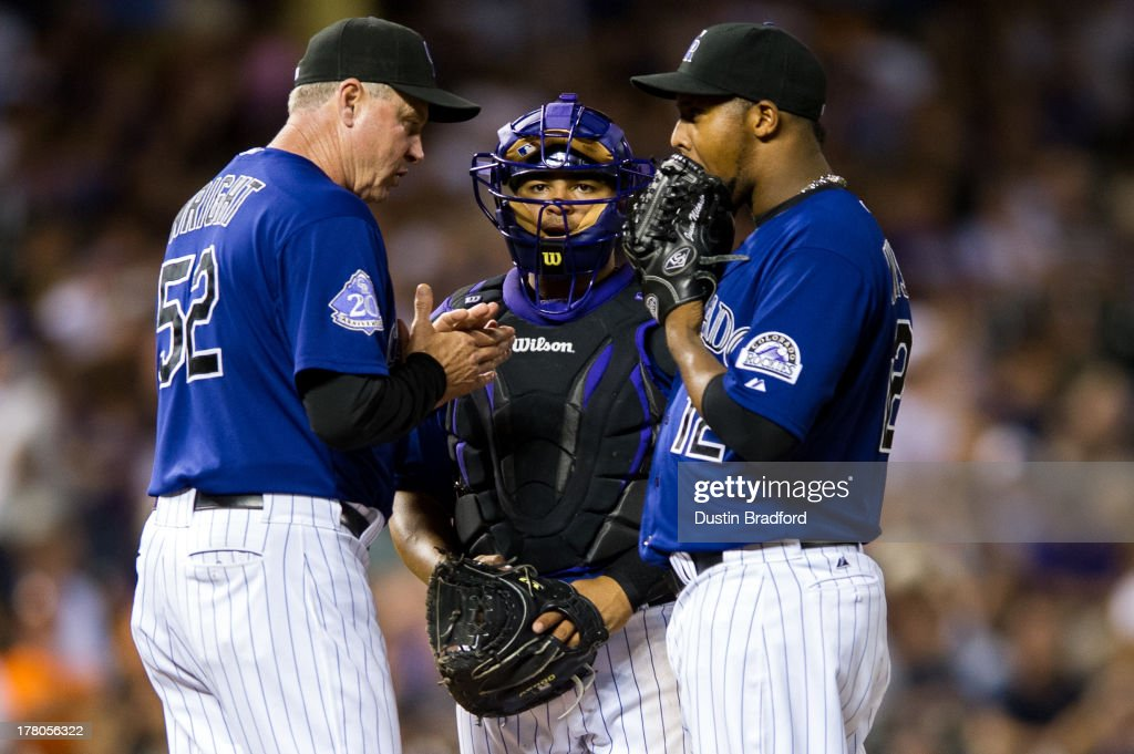 pitching coach Jim Wright #52 and <a gi-track='captionPersonalityLinkClicked' href=/galleries/search?phrase=Wilin+Rosario&family=editorial&specificpeople=5734314 ng-click='$event.stopPropagation()'>Wilin Rosario</a> #20 visit <a gi-track='captionPersonalityLinkClicked' href=/galleries/search?phrase=Juan+Nicasio&family=editorial&specificpeople=6889135 ng-click='$event.stopPropagation()'>Juan Nicasio</a> #12 of the Colorado Rockies on the mound during a game against the San Francisco Giants at Coors Field on August 26, 2013 in Denver, Colorado. The Rockies led 5-0 after six innings.