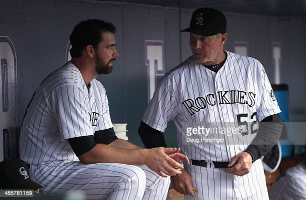 Pitching coach Jim Wright of the Colorado Rockies talks with relief pitcher Boone Logan of the Colorado Rockies in the dugout after being removed...
