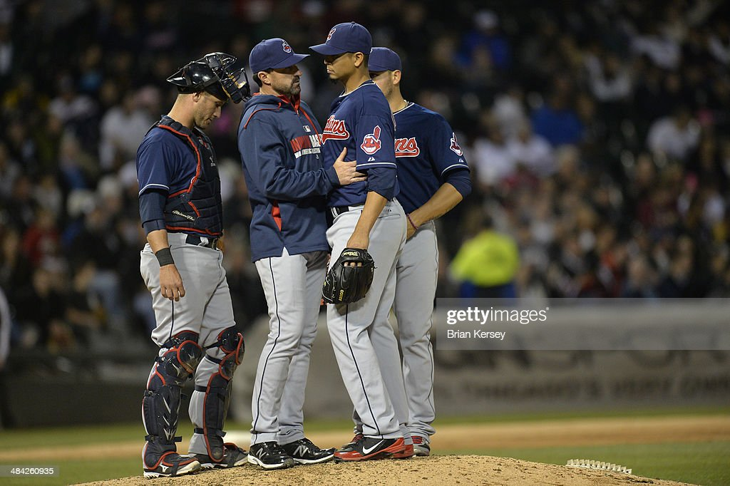 Pitching coach <a gi-track='captionPersonalityLinkClicked' href=/galleries/search?phrase=Mickey+Callaway&family=editorial&specificpeople=3002338 ng-click='$event.stopPropagation()'>Mickey Callaway</a> #32 (c) and catcher <a gi-track='captionPersonalityLinkClicked' href=/galleries/search?phrase=Yan+Gomes&family=editorial&specificpeople=9004037 ng-click='$event.stopPropagation()'>Yan Gomes</a> #10 of the Cleveland Indians (R) talk with starting pitcher Carlos Carrasco #59 during the fifth inning against the Chicago White Sox at U.S. Cellular Field on April 11, 2014 in Chicago, Illinois.