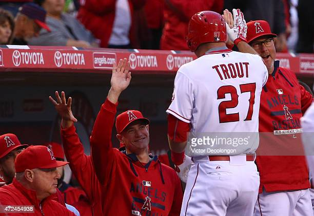 Pitching Coach Mike Butcher high fives Mike Trout of the Los Angeles Angels of Anaheim in the dugout after Trout hit a solo homerun in the first...