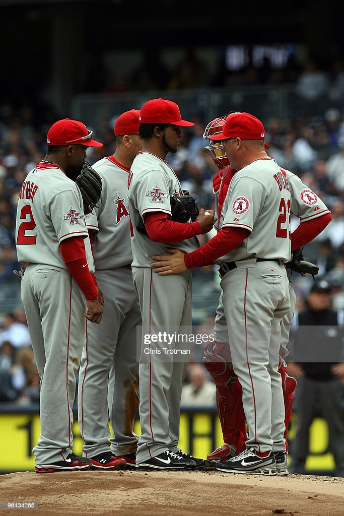 Pitching coach Mike Butcher #23 talks with starting pitcher <a gi-track='captionPersonalityLinkClicked' href=/galleries/search?phrase=Ervin+Santana&family=editorial&specificpeople=243096 ng-click='$event.stopPropagation()'>Ervin Santana</a> #54 of the Los Angeles Angels of Anaheim during a visit to the mound against the New York Yankees during the Yankees home opener at Yankee Stadium on April 13, 2010 in the Bronx borough of New York City.