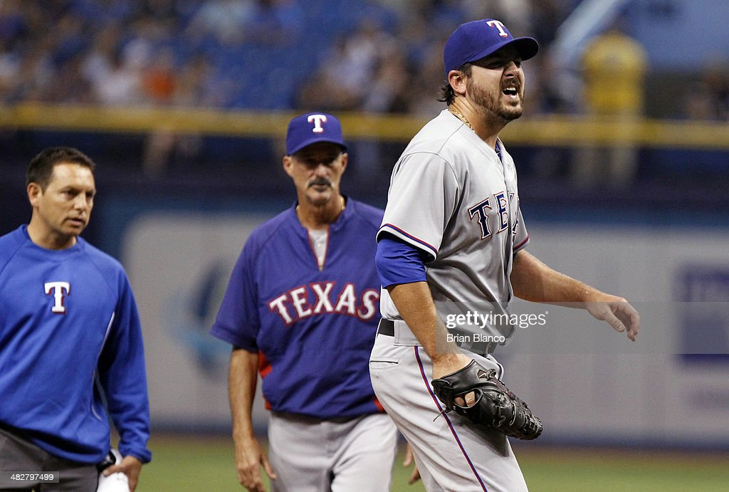 Pitching coach Mike Maddux #31 of the Texas Rangers (C) looks on with a member of the team's medical staff (L) as they watch pitcher Joe Saunders of the Texas Rangers (R) react in pain after throwing a test pitch right after being hit by a batted ball by Evan Longoria of the Tampa Bay Rays during the fourth inning of a game on April 4, 2014 at Tropicana Field in St. Petersburg, Florida. Saunders came off the mound and was replaced by pitcher Daniel McCutchen of the Texas Rangers.
