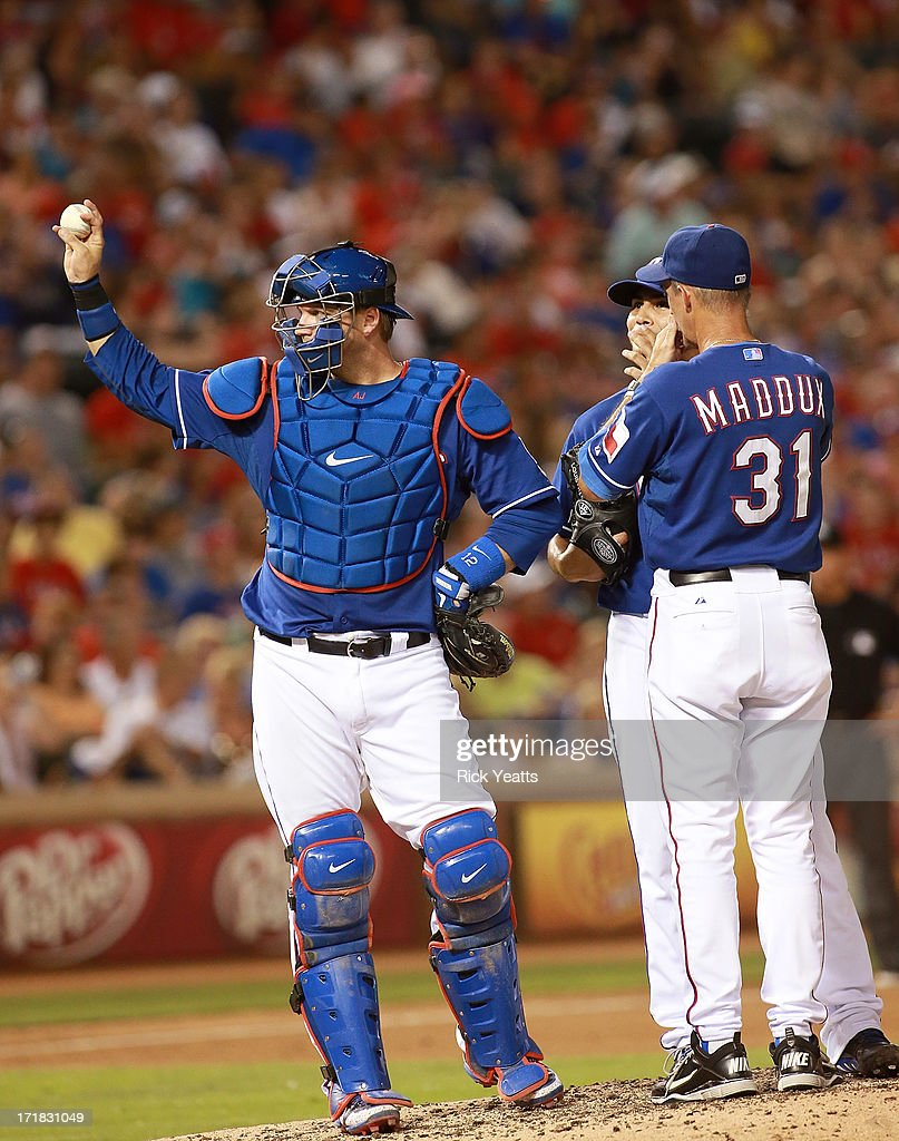 Pitching coach <a gi-track='captionPersonalityLinkClicked' href=/galleries/search?phrase=Mike+Maddux&family=editorial&specificpeople=556746 ng-click='$event.stopPropagation()'>Mike Maddux</a> #31 of the Texas Rangers talks with teammate Martin Perez #33 as <a gi-track='captionPersonalityLinkClicked' href=/galleries/search?phrase=A.J.+Pierzynski&family=editorial&specificpeople=204486 ng-click='$event.stopPropagation()'>A.J. Pierzynski</a> #12 motions the umpire for a new ball in the seventh inning of the game against the Cincinnati Reds at Rangers Ballpark in Arlington on June 28, 2013 in Arlington, Texas.