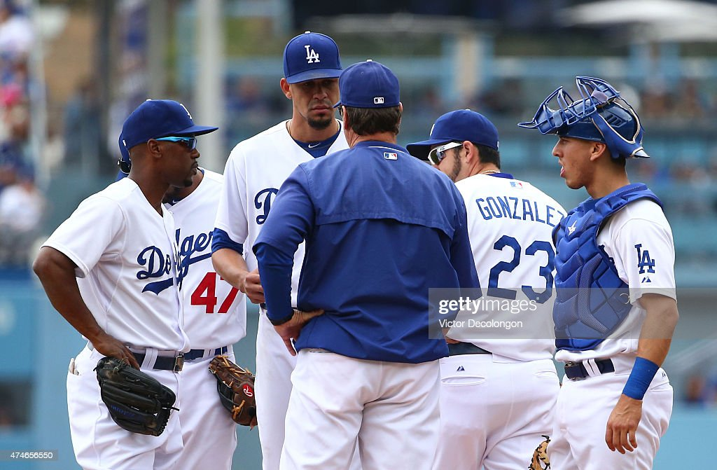 Pitching coach Rick Honeycutt visits the mound to talk to pitcher Carlos Frias as Jimmy Rollins Adrian Gonzalez and catcher Austin Barnes look on in...
