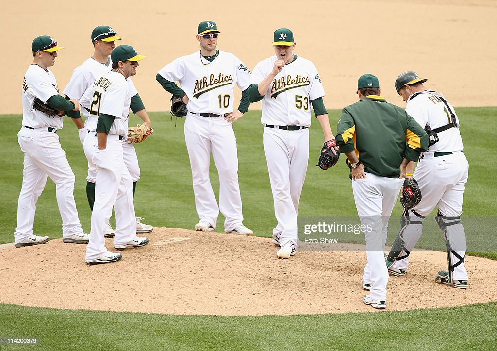 Pitching coach Ron Romanick comes out to talk to Trevor Cahill #53 of the Oakland Athletics and his teammates in the seventh inning against the Chicago White Sox at Oakland-Alameda County Coliseum on May 15, 2011 in Oakland, California.