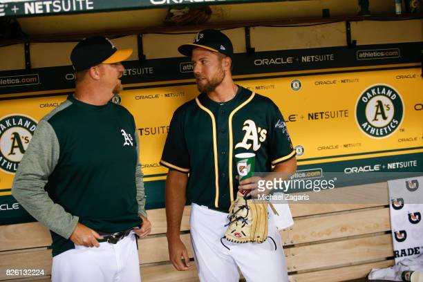 Pitching Coach Scott Emerson and Blake Treinen of the Oakland Athletics talk in the dugout during the game against the Tampa Bay Rays at the Oakland...