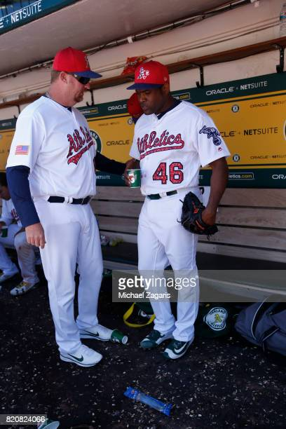Pitching Coach Scott Emerson and Santiago Casilla of the Oakland Athletics alk in the dugout during the game against the Atlanta Braves at the...