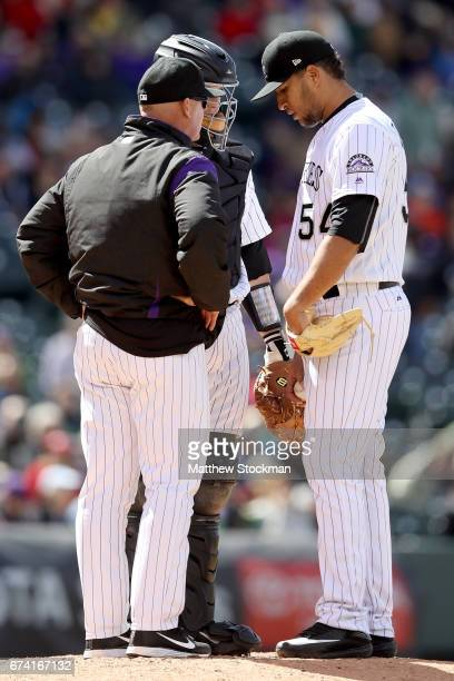Pitching coach Steve Foster catcher Dustin Garneau and pitcher Carlos Estevez of the Colorado Rockies confer on the mound in the seventh inning...