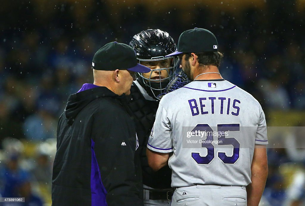 Pitching coach Steve Foster #56, catcher Nick Hundley #4 and pitcher Chad Bettis #35 of the Colorado Rockies confer on the mound after Bettis gave up a run on a single by Yasmani Grandal #9 of the Los Angeles Dodgers (not in photo) in the fifth inning during the MLB game at Dodger Stadium on May 14, 2015 in Los Angeles, California.