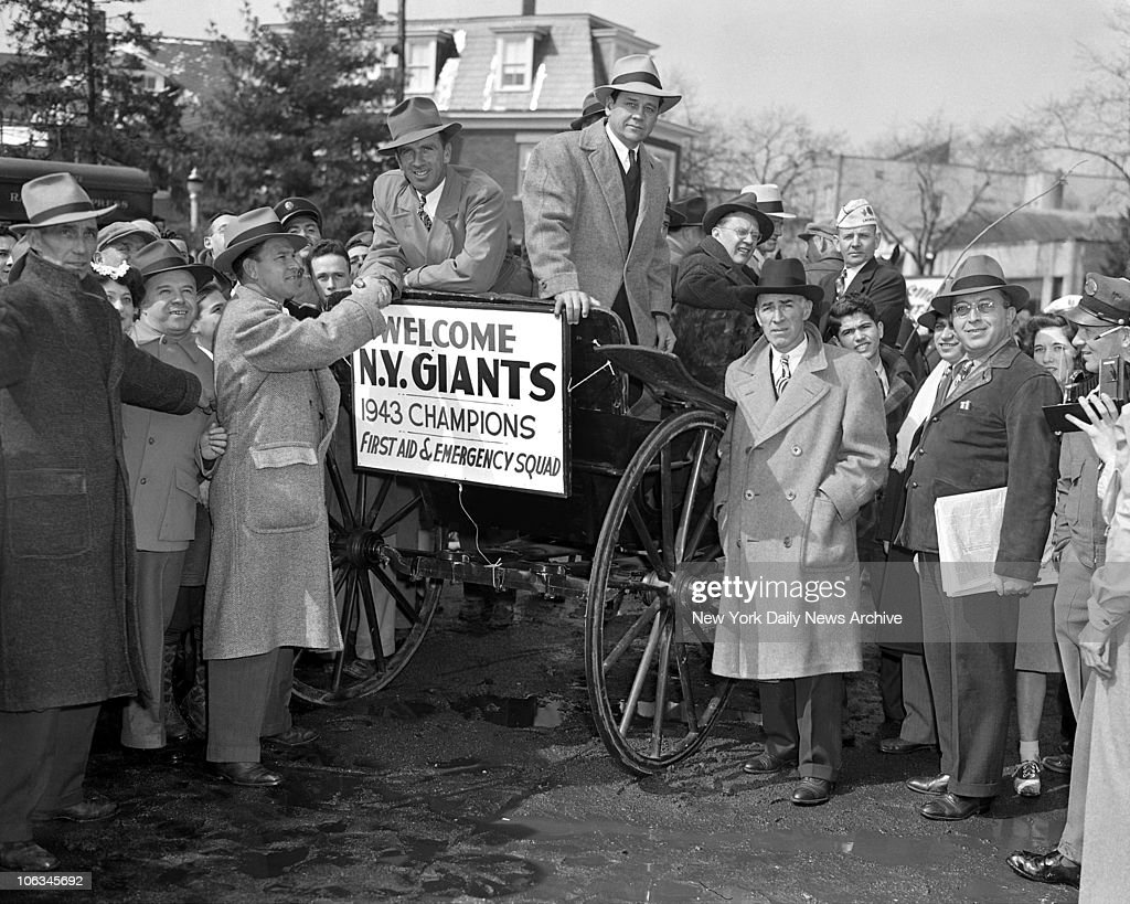 Pitching the New Camp Grounds Who can pitch camp better than a pitcher? In answer to that, New York Giants manager Mel Ott (left) extend the glad hand to hurler Carl Hubbell (in carriage). Flanking Hub is batterymate Gus Mancuso, Secretary Eddie Brannick stands by.