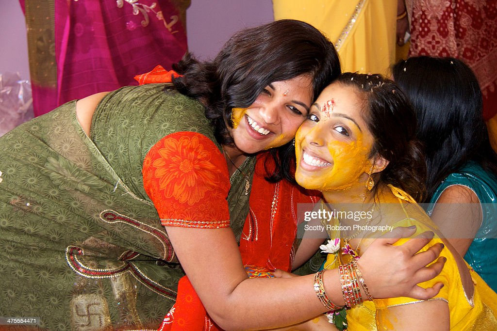 Pithi covered cousin sisters hug in celebration