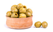 Pitted and marinated green olives in wooden bowl, isolated on white background