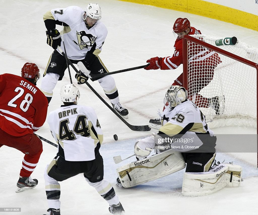 Pittsburgh Penguins' Brooks Orpik (44), Paul Martin (7) and Marc-Andre Fleury (29) defend the goal against Carolina Hurricanes' Alexander Semin (28) and Nathan Gerbe (14) during the third period at the PNC Arena in Raleigh, North Carolina, on Monday, October 28, 2013.