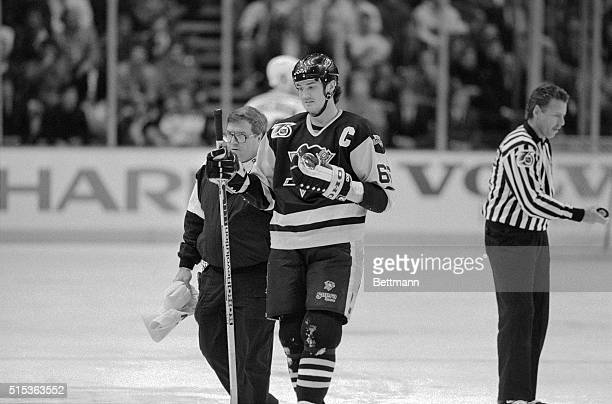 Pittsburgh Penguins Captain Mario Lemieux is escorted off the ice by trainer S Thayer after taking a slash on the wrist from the New York Ranger's...
