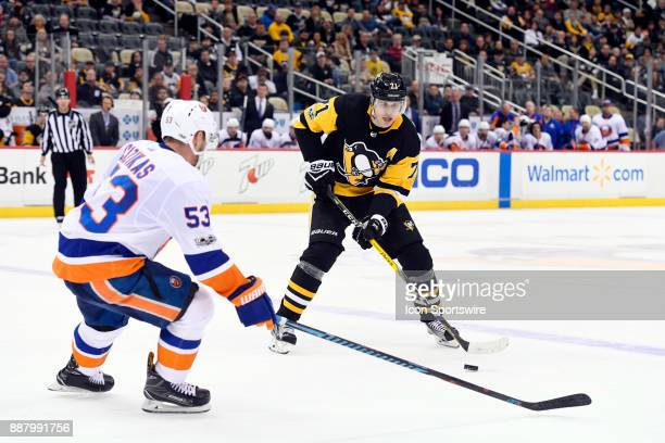 Pittsburgh Penguins Center Evgeni Malkin handles the puck in front of New York Islanders Center Casey Cizikas during the overtime period in the NHL...