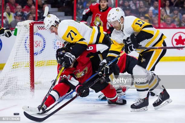 Pittsburgh Penguins Center Evgeni Malkin jumps on Ottawa Senators Defenceman Chris Wideman and Pittsburgh Penguins Right Wing Bryan Rust reaches in...