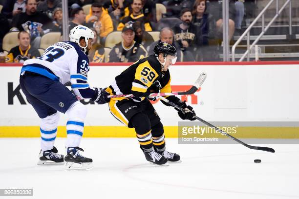 Pittsburgh Penguins center Jake Guentzel skates with the puck as Winnipeg Jets Defenseman Dustin Byfuglien defends during the overtime period in the...