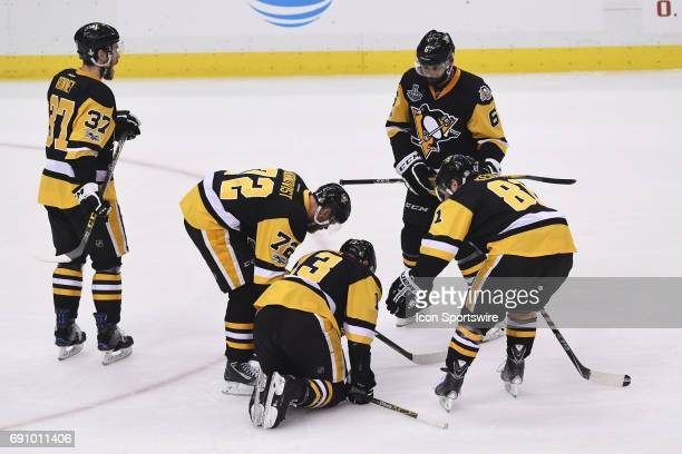 Pittsburgh Penguins center Nick Bonino struggles to get up as teammates look on during the first period in Game Two of the 2017 NHL Stanley Cup Final...