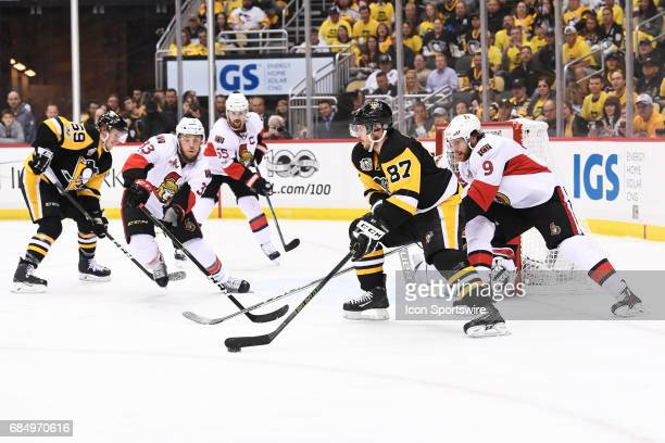 Pittsburgh Penguins Center Sidney Crosby controls the puck as Ottawa Senators right wing Bobby Ryan and Ottawa Senators defenseman Fredrik Claesson...