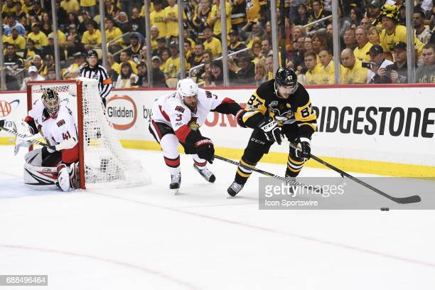 Pittsburgh Penguins Center Sidney Crosby moves the puck as Ottawa Senators defenseman Marc Methot defends in front of Ottawa Senators goalie Craig...