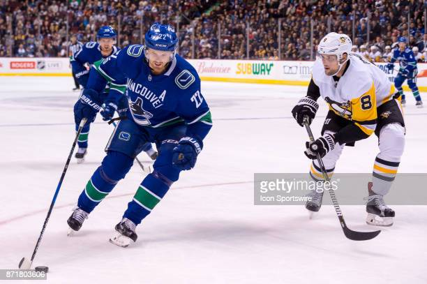 Pittsburgh Penguins Defenceman Brian Dumoulin defends against Vancouver Canucks Left Wing Daniel Sedin during their NHL game at Rogers Arena on...