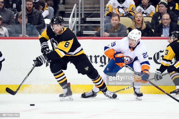 Pittsburgh Penguins Defenseman Brian Dumoulin moves the puck around New York Islanders Center Brock Nelson during the third period in the NHL game...