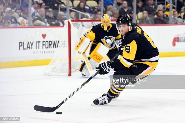Pittsburgh Penguins Defenseman Brian Dumoulin turns with the puck during the third period in the NHL game between the Pittsburgh Penguins and the...