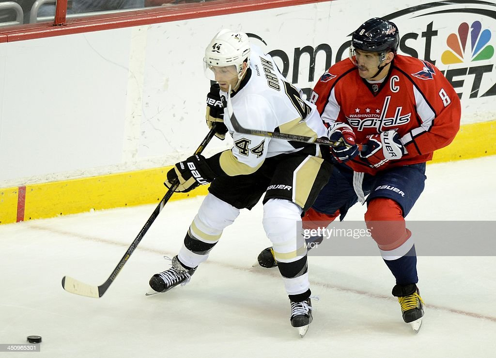 Pittsburgh Penguins defenseman Brooks Orpik (44) works the puck away from backchecking Washington Capitals right wing Alex Ovechkin (8) in the third period at the Verizon Center in Washington, Wednesday, Nov, 20, 2013. The Penguins beat the Capitals, 4-0.