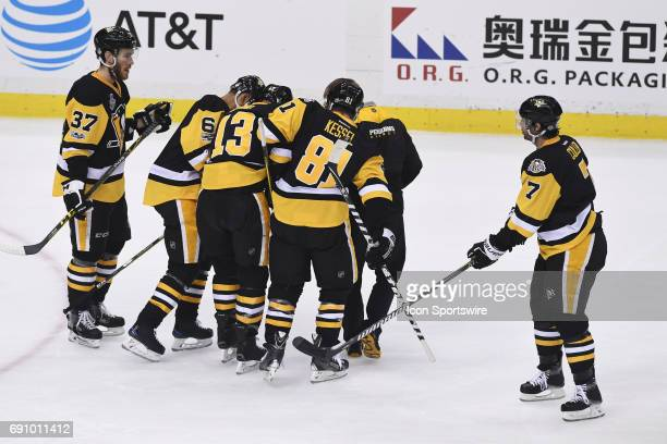 Pittsburgh Penguins defenseman Trevor Daley and right wing Phil Kessel help center Nick Bonino off the ice during the first period in Game Two of the...