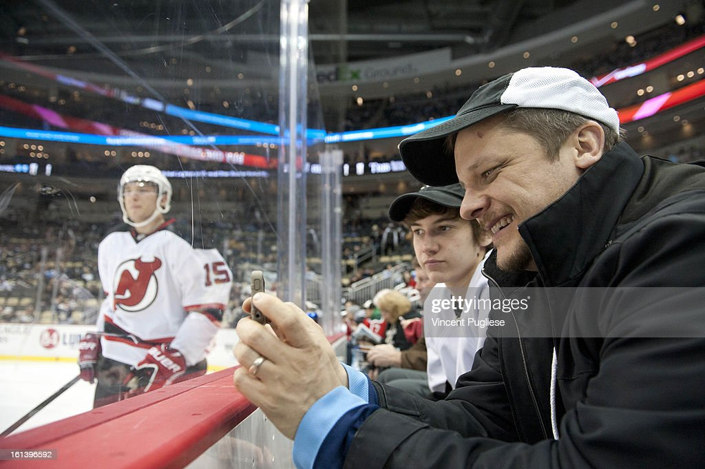 Pittsburgh Penguins fan David Burke takes pictures with his phone while the New Jersey Devils warm up prior to their game on February 10, 2013 at the CONSOL Energy Center in Pittsburgh, Pennsylvania.